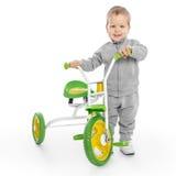 Niño pequeño al lado del triciclo Imagen de archivo
