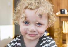 Niño pequeño cuya cara se mancha con la pintura Foto de archivo