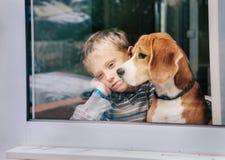 Niño pequeño del dolor con el mejor amigo que mira a través de ventana Foto de archivo libre de regalías