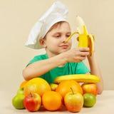 Niño pequeño en el sombrero de los cocineros que pela el plátano fresco en la tabla con las frutas Imagen de archivo libre de regalías