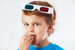Niño pequeño en los vidrios 3D que come algo Foto de archivo