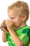 Niño pequeño en una camiseta verde que bebe feliz té Foto de archivo libre de regalías