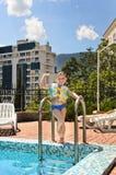 Niño pequeño feliz que agita en el poolside de la cámara Foto de archivo