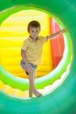 Niño pequeño lindo, jugando en un anillo plástico del cilindro del balanceo, ful Imagen de archivo