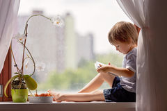 Niño pequeño lindo, sentándose en la ventana, playin en la tableta Fotografía de archivo libre de regalías
