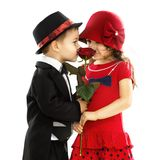 Niño pequeño precioso que da una rosa a la muchacha Imagen de archivo