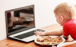 Niño pequeño que come la comida mientras que usa el ordenador portátil en casa Imagenes de archivo