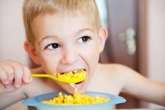 Niño pequeño que come las avenas con leche Imagen de archivo