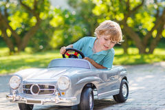 Niño pequeño que conduce el coche viejo del juguete grande, al aire libre Foto de archivo libre de regalías