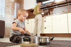 Niño pequeño que juega con cocinar los crisoles Foto de archivo libre de regalías