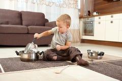 Niño pequeño que juega con cocinar los crisoles Imagen de archivo libre de regalías