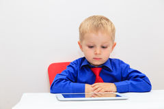 Niño pequeño que lleva el lazo y que mira tacto Imagenes de archivo