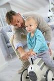 Niño pequeño que monta el juguete retro del coche con su padre Imágenes de archivo libres de regalías