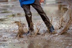 Niño pequeño que salpica en un charco de fango, Foto de archivo libre de regalías
