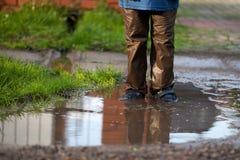 Niño pequeño que salpica en un charco de fango, Fotografía de archivo libre de regalías