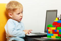 Niño pequeño que usa el ordenador de la PC del ordenador portátil en casa Imágenes de archivo libres de regalías