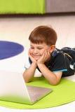 Niño pequeño que usa el ordenador en el país Imágenes de archivo libres de regalías