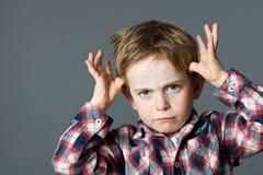 Niño pequeño rojo descontentado del pelo que imita para la cosa tonta Fotos de archivo