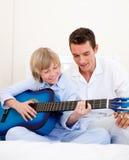 Niño pequeño sonriente que toca la guitarra con su padre Foto de archivo libre de regalías