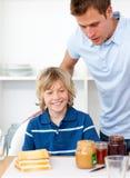 Niño pequeño y su padre que preparan el desayuno Imagen de archivo
