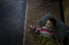 Niño pobre que duerme en piso de la casa de los abuelos Imagen de archivo