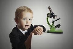 Niño poco muchacho del scientistlittle en lazo Colegial que trabaja con un microscopio Educación Imagenes de archivo
