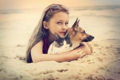 Niño que abraza animales domésticos Imagen de archivo