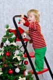 Niño que adorna el árbol de navidad Fotos de archivo libres de regalías