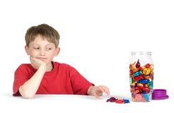 Niño que alcanza para el caramelo Foto de archivo libre de regalías