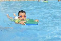 Niño que aprende nadar en verano Imagen de archivo libre de regalías