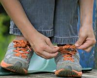 Niño que ata el zapato de gimnasio Imágenes de archivo libres de regalías
