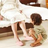 Niño que ayuda a la mujer mayor en casa Fotos de archivo