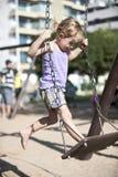 Niño que balancea en el oscilación, patio urbano Imagen de archivo libre de regalías