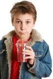 Niño que bebe el zumo de fruta fresca a través de una paja Imagen de archivo libre de regalías