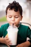 Niño que bebe a través de una paja Foto de archivo libre de regalías