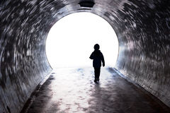 Niño que camina en la luz Imagenes de archivo