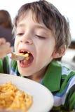 Niño que come el mac y el queso Fotos de archivo libres de regalías
