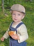Niño que come el rodillo en el parque al aire libre Imagen de archivo libre de regalías