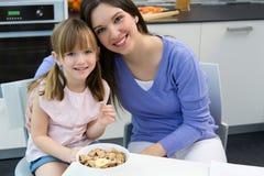 Niño que come los cereales con su mamá en la cocina Imagen de archivo