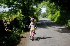 Niño que completa un ciclo una bici Imagen de archivo libre de regalías