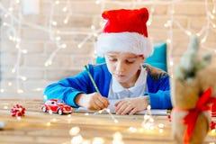 Niño que escribe una letra a Santa Claus en casa Imagen de archivo libre de regalías