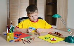 Niño que hace decoraciones de la Navidad Haga la decoración de la Navidad con sus propias manos Fotos de archivo libres de regalías