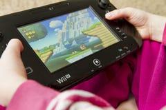 Niño que juega al juego Mario Bros estupendo de Wii U Imágenes de archivo libres de regalías