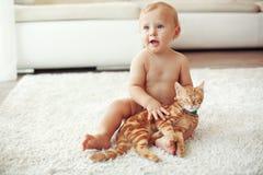Niño que juega con el gato Imagenes de archivo