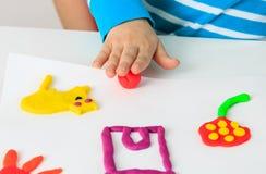 Niño que juega con formas del moldeado de la arcilla Imagen de archivo