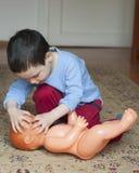 Niño que juega con la muñeca Foto de archivo libre de regalías