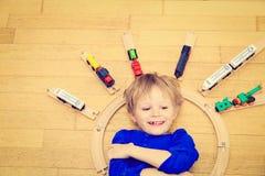 Niño que juega con los trenes interiores Imagenes de archivo