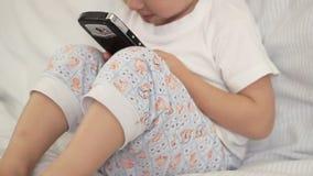 Niño que juega con un smartphone mientras que se sienta metrajes