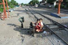 Niño que juega en vías del tren en la estación Sangkrah Java Indonesia central a solas Imágenes de archivo libres de regalías