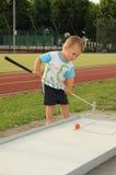 Niño que juega a mini golf Fotografía de archivo libre de regalías
